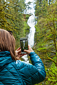 A young woman takes a picture of Munson Creek Falls with her smartphone in Munson Creek Falls State Natural Site