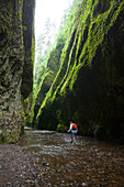 Icy cold, ankle-deep waters and a log jam can't keep this man from exploring Oregon's Oneonta Gorge, an emerald green treasure outside of Portland.