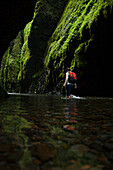 It's emerald green walls beckon a woman to overcome the icy cold water and  explore more deeply into Oregon's Oneonta Gorge.