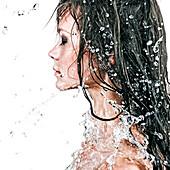 Face of Caucasian girl splashing in water