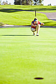 Caucasian woman planning putt on green at golf course