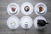 Teapot and plates of dessert on lace doilies