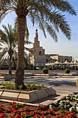 Palm trees and flower beds along Al-Corniche, waterfront promenade, with Qatar Islamic Cultural Centre, Doha, Qatar, Middle East