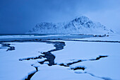 Snowy landscape on the beach of Flakstad with the peak of Hustinden (691 m) in winter, Flakstadøya, Lofoten, Norway, Scandinavia