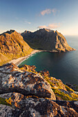 Wide view from top of Ryten to the sandy beach of Kvalvika bay and the surrounding mountains in the last evening light, Moskenesøy, Lofoten, Norway, Scandinavia