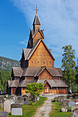 Heddal stave church with path and grave stones in summer, Notodden, Telemark, Norway, Scandinavia
