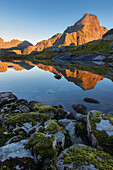 Sunrise over the foremost Lofoten island Moskenesøy with the illuminated peak of Hermannsdalstinden (1029 m ) and it's reflection in a small mountain lake, Lofoten, Norway, Scandinavia