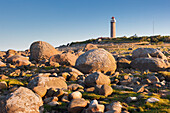 Lighthouse Lista fyr between large rocks in the morning sun, Farsund, Vest-Agder, Norway, Scandinavia