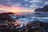 Impressive sunset above the Okshornan cliffs on Ersfjordr in northern Norway, approaching waves in the foreground, Island of Senja, Troms Fylke, Norway, Scandinavia