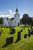Ulvik church with blue sky, flowers and graves in the summer, Hardangerfjord, Hordaland, Norway, Scandinavia
