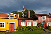 View of colorful houses in the Bohemian district Bakklandet with the Church Bakke Bydelshus in the background, Nygata, Trondheim, Sør-Trøndelag, Norway, Scandinavia