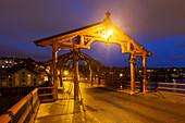View of the illuminated wooden bridge Gamle Bybroen in the historic center of Trondheim at dusk, Trondheim, Sør-Trøndelag, Norway, Scandinavia