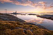 Romantic sunset above the lighthouse Tranøy Fyr on the coast of the Vest Fjord with the Lofoten wall in the background, Tranøya, Hamarøy, Nordland, Norway, Scandinavia