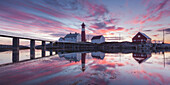 Panorama of a picturesque sunset above the lighthouse Tranøy Fyr in summer with it's reflection in the ocean, Tranøya, Hamarøy, Nordland, Norway, Scandinavia