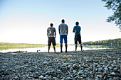 Three young men standing at a lake, Freilassing, Bavaria, Germany
