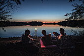 Three young men lying at a lake and enjoying the nature, Freilassing, Bavaria, Germany