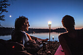 Two young men lying at a lake at night, Freilassing, Bavaria, Germany