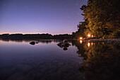 Young men lying at a lake at the edge of a lake at night, Freilassing, Bavaria, Germany