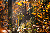 Young man running on a trail through a forest, Allgaeu, Bavaria, Germany