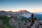 Odle di Eores, Dolomites, South Tyrol, Italy. Hiker admires the sunrise on the Odle