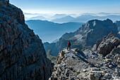 Brenta Dolomites, Trentino, Italy. Mountaineer admiring the view from the via ferrata Bocchette Alte