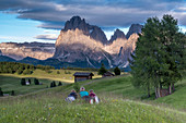 Alpe di SiusiSeiser Alm, Dolomites, South Tyrol, Italy. Mountaineers on the Alpe di Siusi admire the alpenglow. In the background the Sella, SassolungoLangkofel and SassopiattoPlattkofel