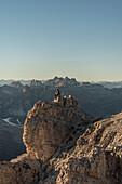 Puez, Odle, Lagazuoi mount, Falzarego Pass, Cortina d'Ampezzo, Dolomiti, Dolomites, Belluno, Veneto, Italy. Hiker looking at panorama from Lagazuoi.