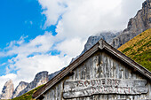 ' A timber house with carved label ''Souvenir Dolomiti'' as a souvenir shop in fornt of the mountain scenery at the Sellajoch, Canazei, the Dolomites, South Tirol, Alto Adige, Italy'