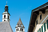 The towers of the parish church Saint Andreas and in the background of the church Liebfrauenkirche and a town house with window shutters in the Old Town, Kitzbühel, Tyrol, Austria