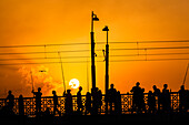 Silhouette, angler and pedestrian on the Galata bridge during sunset, Istanbul, Turkey