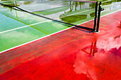 Red and green coloured tennis hard court after a rain with reflexions, Hamilton, Island Bermudas, Great Britain