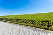 A typical German wooden lattice fence seperates the way with interlocking pavement from the dyke, Juist, Schleswig Holstein, Germany
