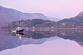 Yachts moored on a mirror still Loch Leven during twilight, Glencoe, Highland, Scotland, United Kingdom, Europe