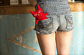 Rear view of a teenager girl with a red ugly doll in the shorts pocket.
