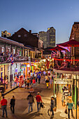 Crowds of visitors walk along Bourbon Street in the Fench Quarter twilight enjoying the nightlife of New Orleans, Lousiana