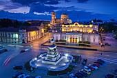 Bulgaria, Sofia, Ploshtad Narodno Sabranie Square, Statue of Russian Tsar Alexander II, National Assembly building, and Alexander Nevski Cathedral, elevated view, dusk.