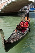 Richly decorated red gondola, with gondolier, on canal, bridge Cannaregio or delle Guglie in the background, Venice, Italy.