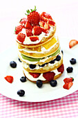 Stack of pancakes with berries and White cream on a white plate, Hong Kong, China, Asia