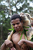 Kombai man coming back from a successful hunt with a wild pig on the back, Papua, Indonesia, Southeast Asia.