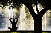 Woman practicing Yoga, Riera Park, Palma, Mallorca, Balearic Islands, Spain.