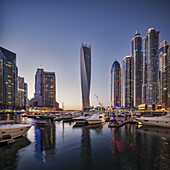 Dubai Marina at twilight with the Cayan Tower (Infinity Tower), the Dubai Marriott Harbour Hotel and Suites and various residential towers, Dubai Marina, Dubai, The United Arab Emirates.