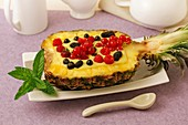 Stuffed pineapple with custard and berries.