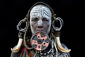 Portrait of woman of the Mursi tribe traditionally decorated and painted, wearing a large clay lipplate, Omo Valley, Ethiopia, Africa.