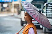 Nun on her alms rounds, Yangon, Myanmar.