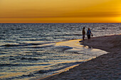 Couple on the beach during sunset at Gulf Shores, Alabama.