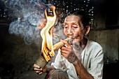 Woman smoking a big cigar made out of corn leaves and tobacco.