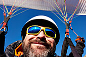 An adult caucasian man while paragliding.