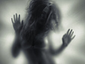 Beautiful young woman blurred silhouette behind glass.