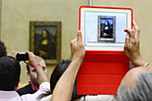 Visitor taking a picture of the Mona Lisa, The Louvre Museum, Paris, France