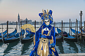 A masked woman at the carnival in Venice with gondolas in the background, Italy, Europe